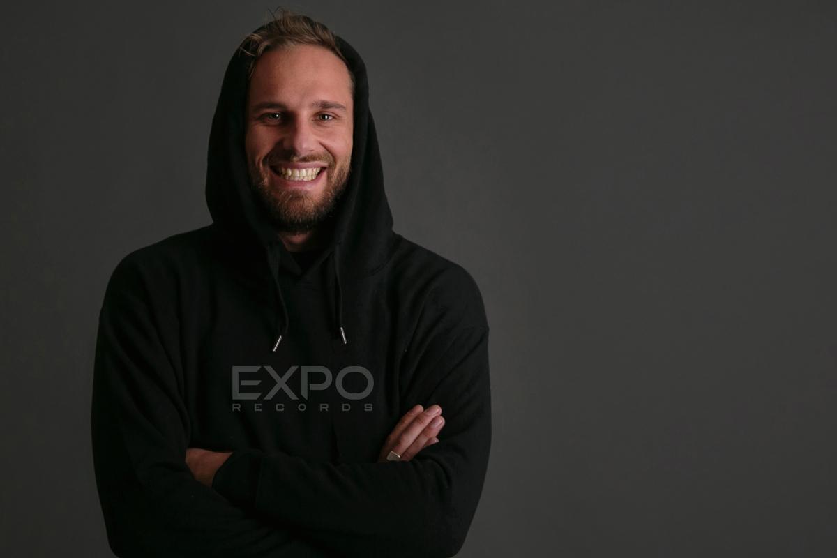Der Künstler Dynamic Range lächelt mit verschränkten Armen in die Kamera. Er trägt einen schwarzen Kapuzenpullover.