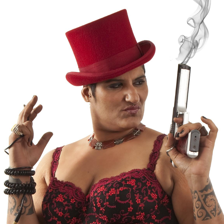 Die Djane Ma Faiza ist frontal zu sehen. Sie trägt ein rotes Korsett und einen roten Zylinder. In der linken Hand hält sie eine rauchende Pistole.
