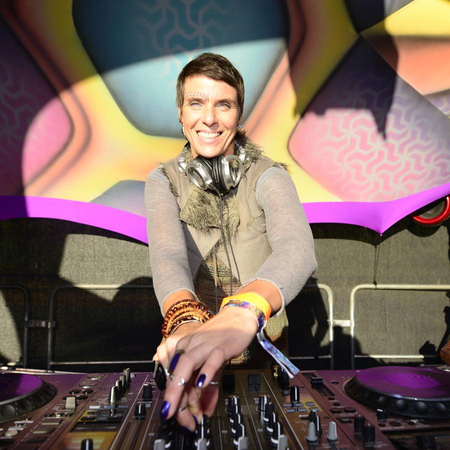 Djane Melburn an den Turntables. Sie lächelt in die Kamera.