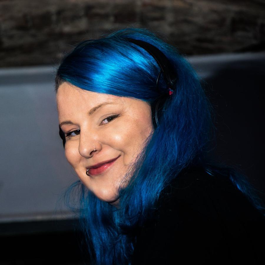 Djane Sati lächelt in die Kamera. Sie hat blaue Haare.