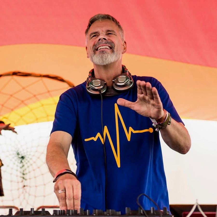 DJ Vargo an den Turntables. Er trägt Kopfhörer um den Hals und schaut Richtung Publikum.