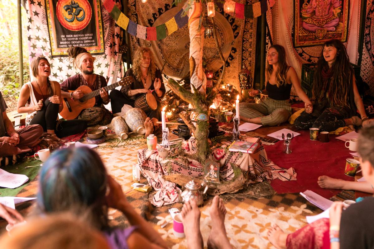In einem Zelt sitz eine Gruppe von Menschen im Kreis. Einer hat eine Gitarre in der Hand.
