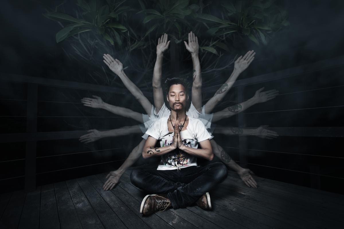 Kenta Hayashi sitzt im Schneidesitz in der Mitte des Bildes. Die Hände hat er vor der Brust zusammengelegt und die Augen sind geschlossen. Durch einen Effekt sieht es so aus, als ob 10 seiner Arme um seinen Körper kreisförmig an seinem Körper verteilt sind.