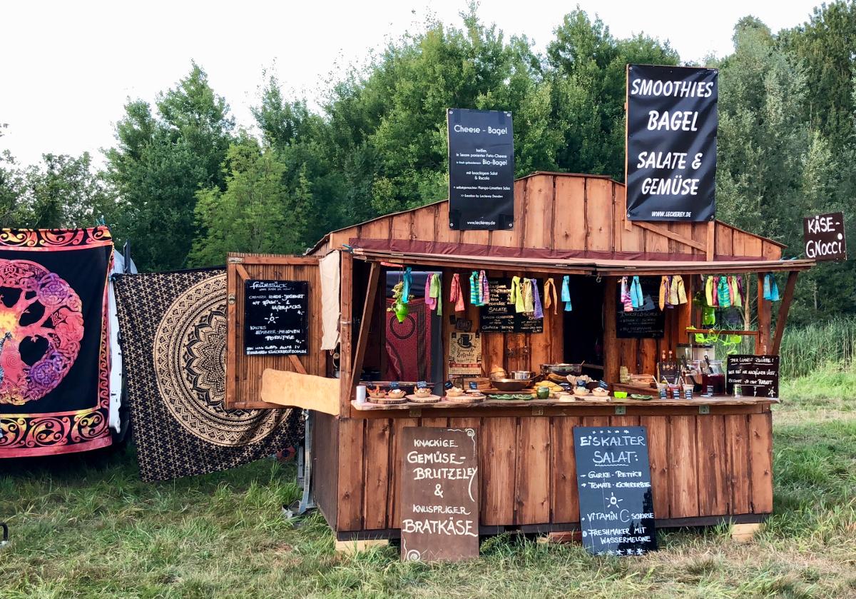 Der Stand der Leckerey auf dem New Healing Festival. Der Stand ist aus Holz und verfügt über 5 Kreidetafeln auf denen die Angebote stehen.