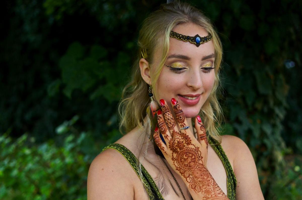 Linda May hat ihre mit Henna bemalte Hand an ihrem Hals liegen