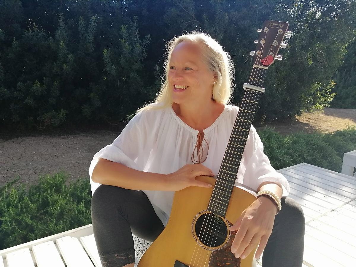 Die Künstlerin sitzt mit der Gitarre vor ihr auf der Terasse. Sie schaut nach links.