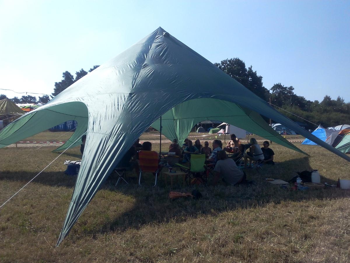 Sternförmiges Zelt unter dem eine Gruppe Menschen sitzt