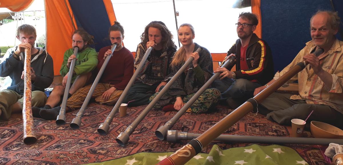 7 Menschen sitzen nebeneinander und spielen auf ihren Didgeridoos.