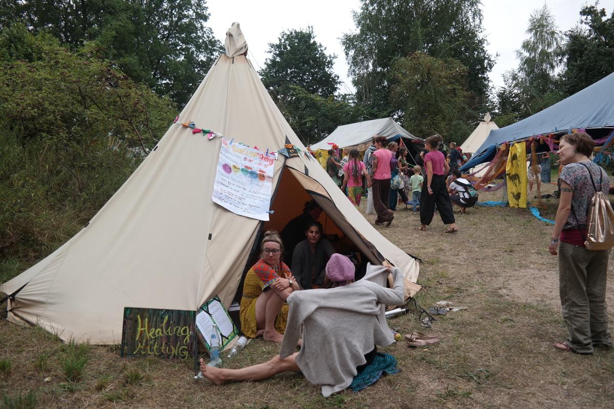 Tipi des Healing Sitting Programms auf dem New Healing Festival. Vor dem Tipi sitzen drei Frauen