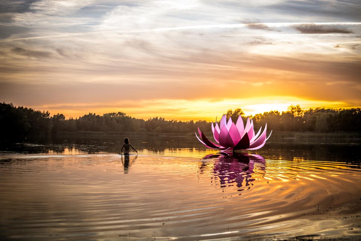 Sonnenuntergang am Badesee Preddöhl. Im See befindet sich ein Kind. Rechts davon ein Skulptur in Form einer Lotusblume.