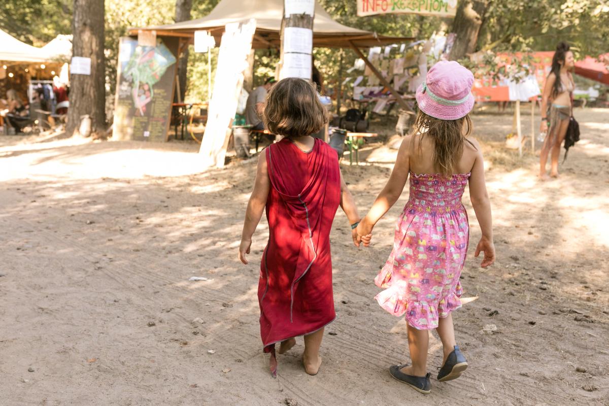 Zwei Kinder von hinten fotografiert, die Hand in Hand über das New Healing festival laufen. Das linke Kind trägt ein rotes Kleid. Das rechte kind trägt ein rosafarbenes Kleid und einen rosa Hut.