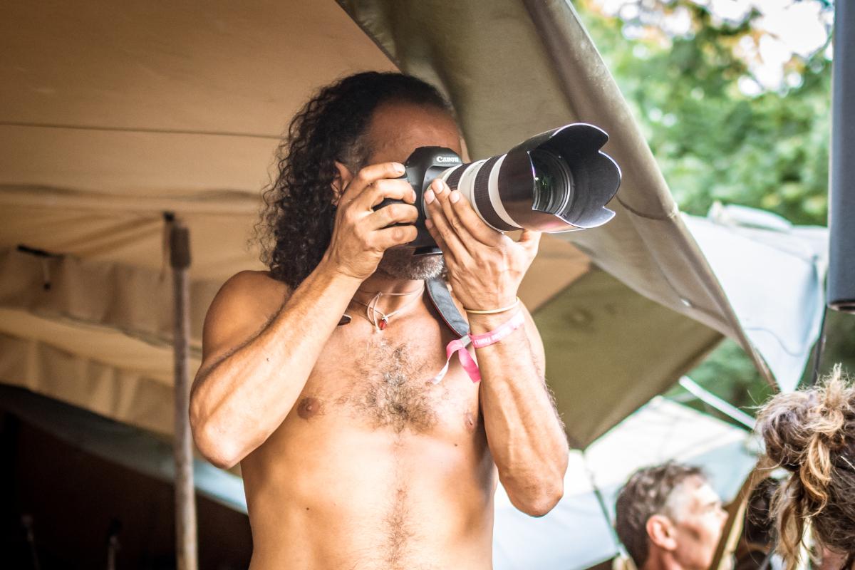 Ein Mann mit mittellangen, gelockten Haaren hält seine Kamera vorm Gesicht, um etwas zu fotografieren.