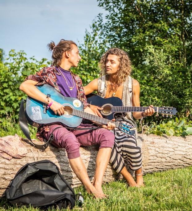 Pit und Carl vom Kinderyoga sitzen auf einem Baumstamm und schauen sich an, während sie Gitarre spielen.