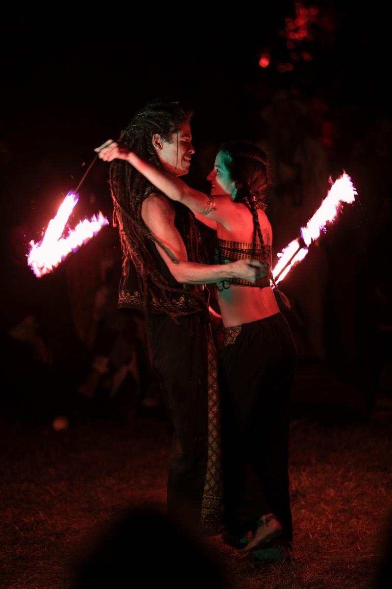 Ein Mann und eine Frau stehen sich mit den Gesichtern zugewandt gegenüber. Sie halten hinter dem Rücken des jeweils anderen eine brennende Schnur. Es ist Nacht