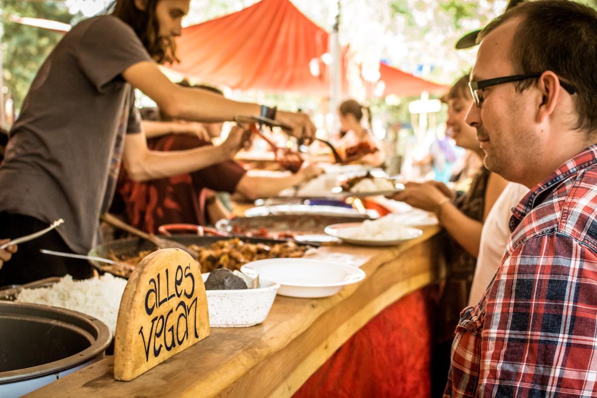 Eine Theke hinter der 3 Menschen Essen ausgeben. Auf der Theke sind ein paar Teller platziert und ein Holzschild auf dem alles vegan steht.