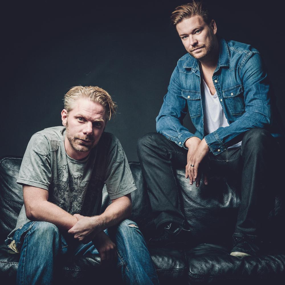 Die beiden Musiker von Ticon sitzen auf einer schwarzen Ledercouch. Der rechte sitzt auf der Lehne, der linke auf dem Sitzpolster.