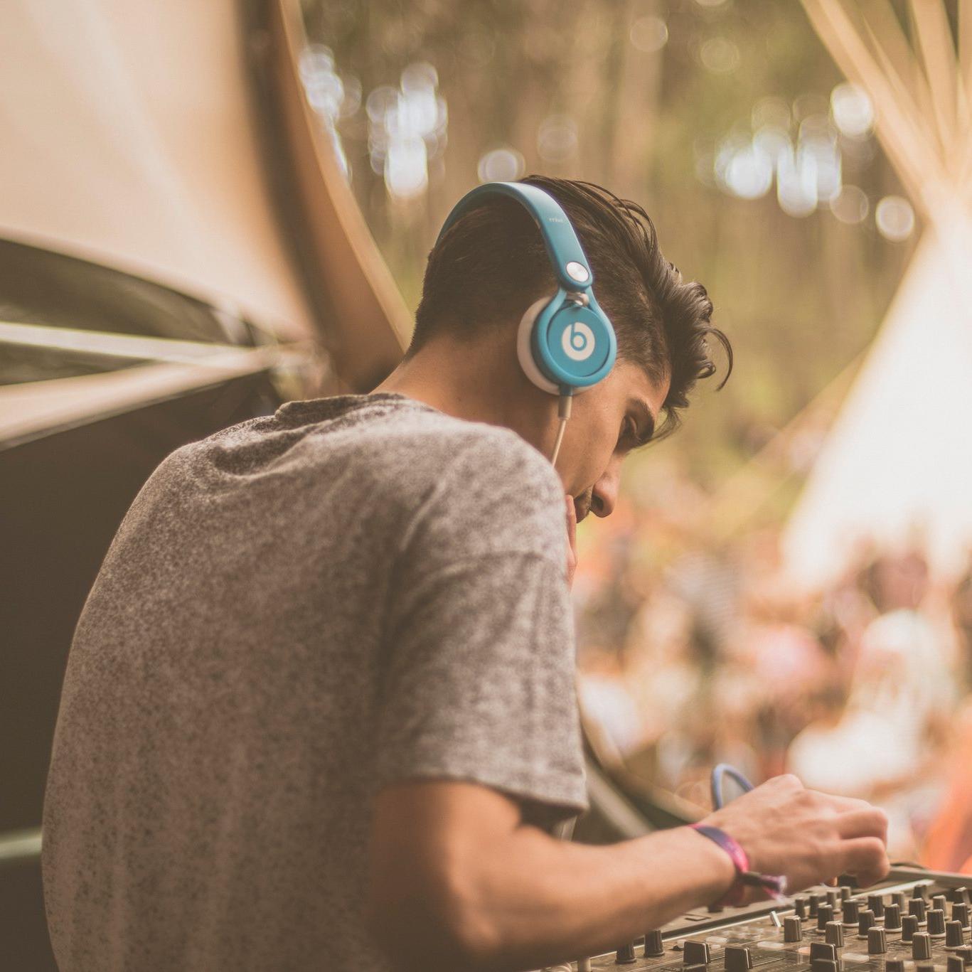 Der DJ Lifeforms an den Turntables. Er hat den Rücken zugewandt und trägt blaue Beats Kopfhörer